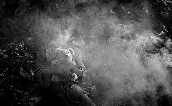 ময়লাস্তূপের ওপরে দাঁড়িয়ে বুকের মধ্যে পুতুল জড়িয়ে ধরে আছে ৮ বছর বয়সী শিশুশ্রমিক পপি। ছবি : শাহনেওয়াজ খান, সিএনএন